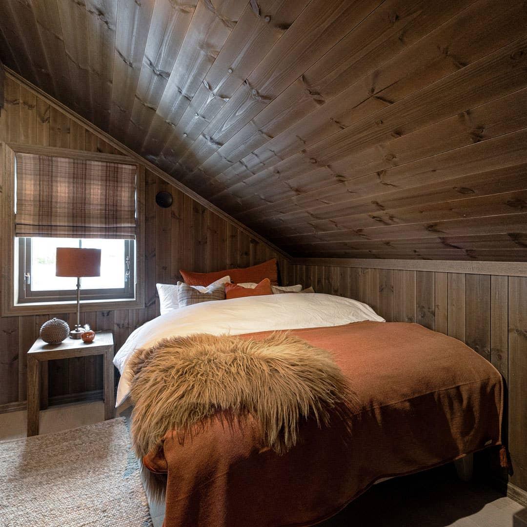 Lune tekstiler, tunge gardiner i rutemønster og en skinnfell på sengen skaper et drømmesoverom på hytta på fjellet. – Mange vil helst sove i sengesett av flanell på hytta, forteller hytteekspert Mia Ytterbøl i Møbelringen.