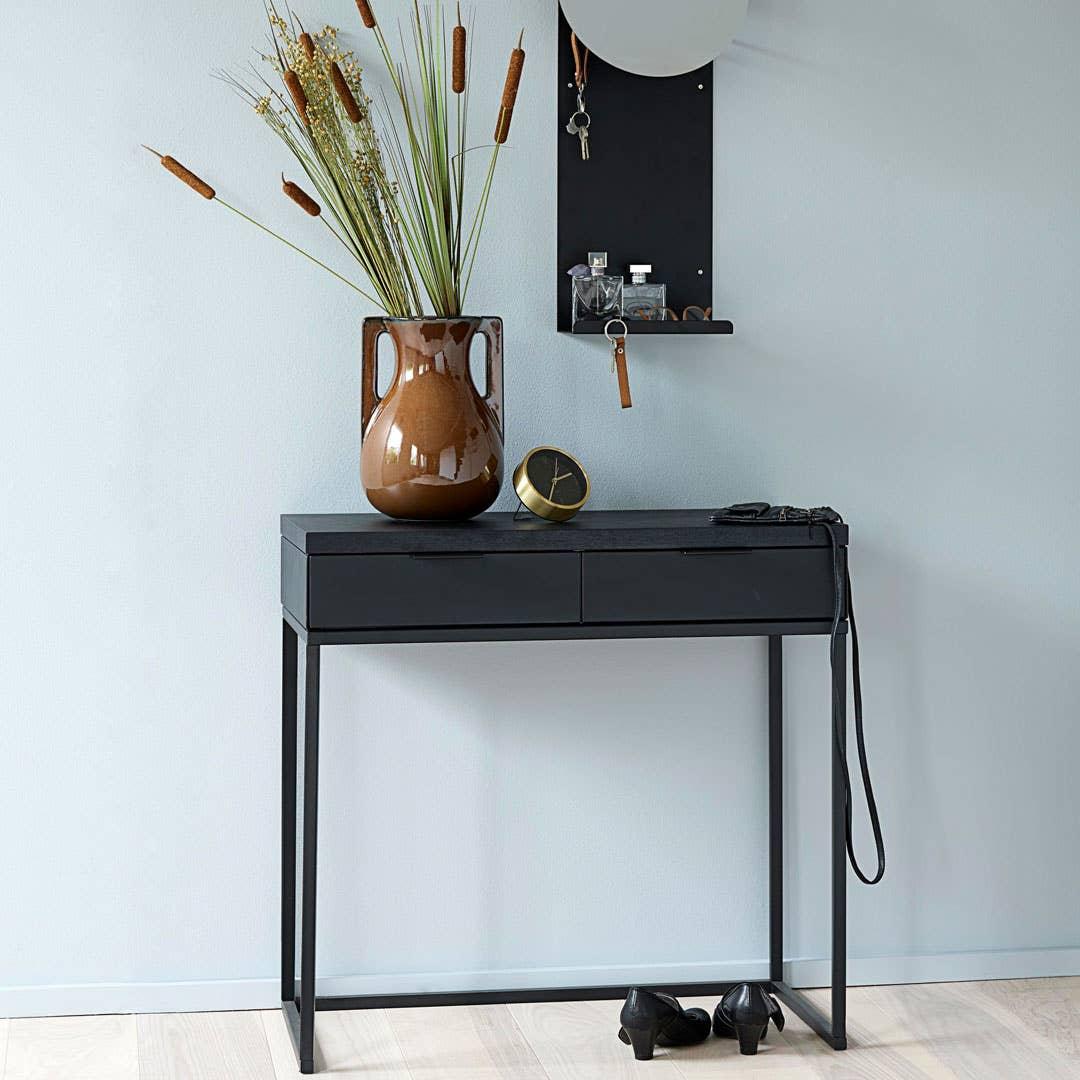 Noir konsollbord. Joy er en møbelserie i matt, sortlakkert metall. Det luftige uttrykket gjør det godt egnet til både små og store entreer. Serien består av konsollbord, hyller, speil og knaggrekker.
