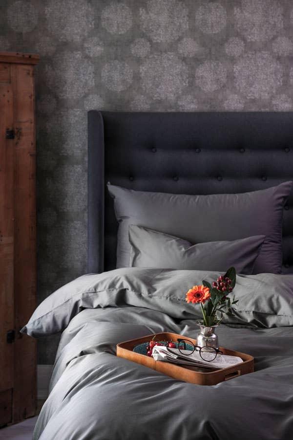 En lekker tapet i en mørk nyanse, gjerne ton-i-ton med tekstiler og sengegavl, vil løfte soverommet. Dersom du er redd det skal bli for voldsomt, kan du teste å tapetsere veggen bak sengen og male de andre veggene i en passende nyanse.