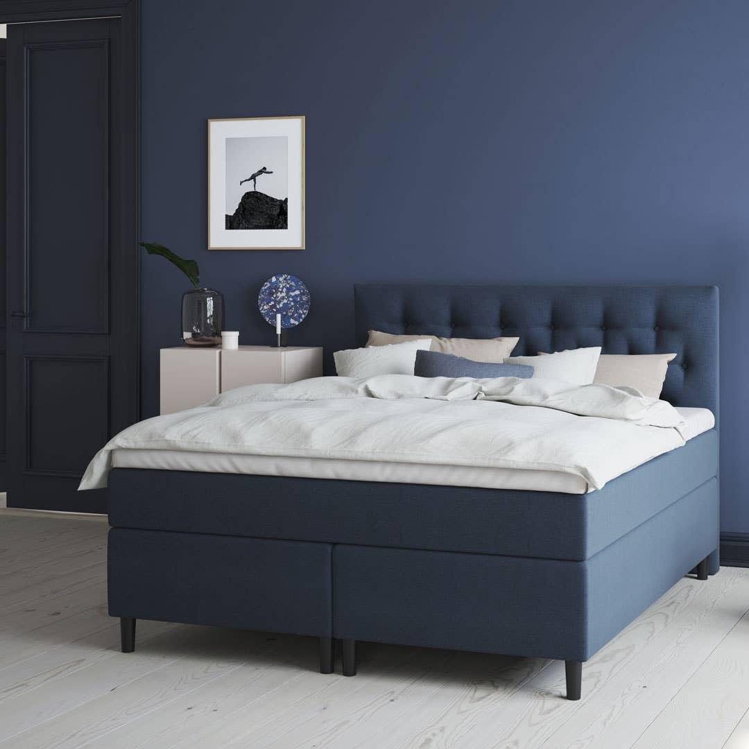 En mørk blå vegg skaper en rolig og behagelig atmosfære på soverommet – gjerne kombinert med sengegavl og tekstiler i samme fargeskala.