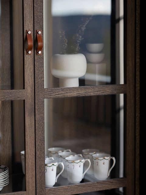 Et nytt vitrineskap fra Woodstory rommer et vakkert gammelt servise på hytta. Glassdørene gjør at skattene dine får stå på utstilling og være dekorelementer i seg selv.