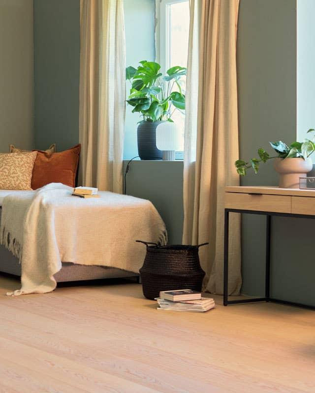 Gardiner som går fra gulv til tak skaper en illusjon av god romfølelse og takhøyde. I en liten leilighet er smarte oppbevaringsløsninger gull verdt – her med skuffer i et nett konsollbord og en myk kurv der et ekstra pledd kan få ligge.