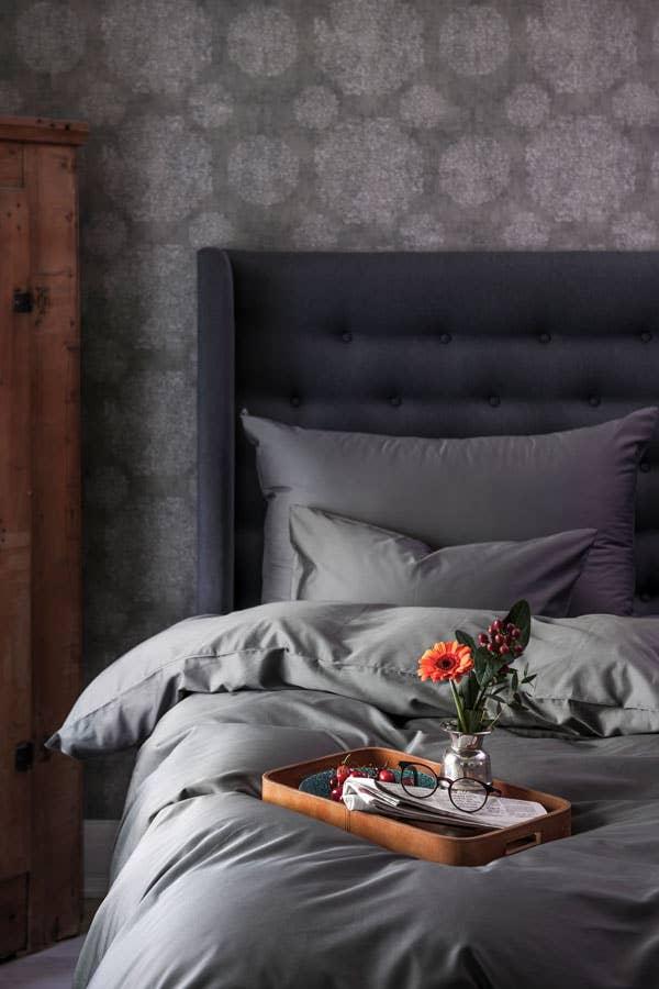 Inspo til et lite soverom! Ulike gråtoner satt sammen med et mønstret tapet i mørkegrå nyanser gir en lun og elegant look på et lite soverom.