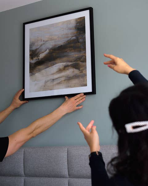 Elmira setter stor pris på å ha en handyman i husholdningen – her får hun hjelp til å henge opp bildet Surface ll fra Møbelringen på soveromsveggen.