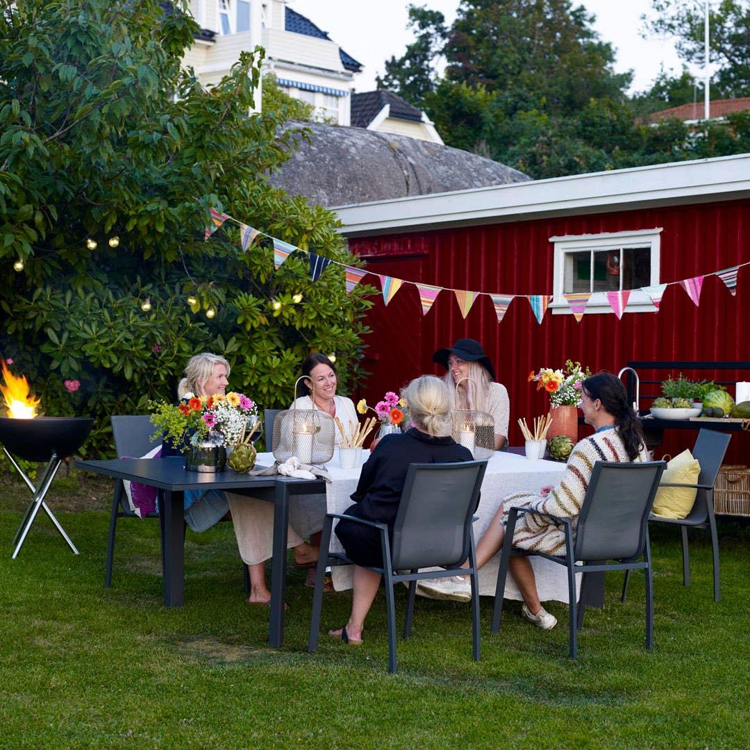 Sommerlige tekstiler, nok sitteplasser, og lyslenker eller levende lys når solen går ned er alt du trenger for å gjøre hagen festklar. Møbler fra Freeport-serien.