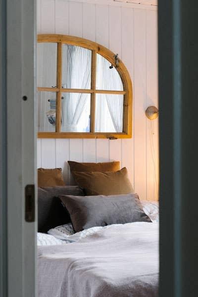 Et gammelt vindu blir et personlig speil over sengen sammen med pynteputer fra Hødnebø®.